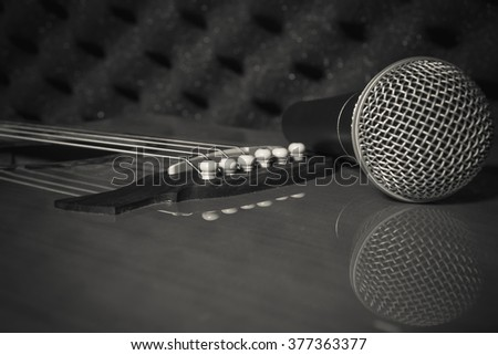selective focus pin of classic guitar in home recording studio.Microphone on classic guitar background. - stock photo