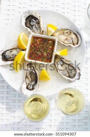 Selective focus point on fresh oysters shell with lemon and glasses of champagne. Top of view - stock photo