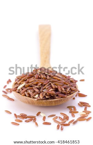 Selective focus Red rice in a wooden spoon on white background - stock photo