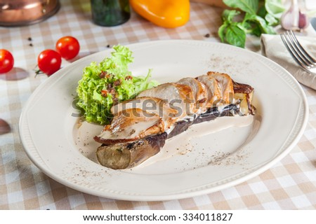 Selective focus roast sliced chicken fillet on an eggplant garnished with creamy sauce and lettuce on  the white plate on the table with ingredients - stock photo