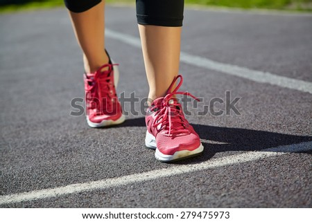 selective focus.. runner feet closeup. athlete running on jogging track at the stadium. running shoes. jogging outdoors - stock photo