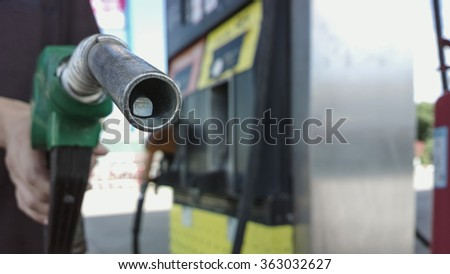 Selective focus The fuel nozzle tip at gas station - stock photo