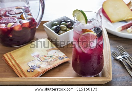 Selective focus was used on this glass filled with refreshing red sangria that includes healthy fresh fruit like peaches, lemons, limes, oranges and berries. It is served with a variety of appetizers. - stock photo