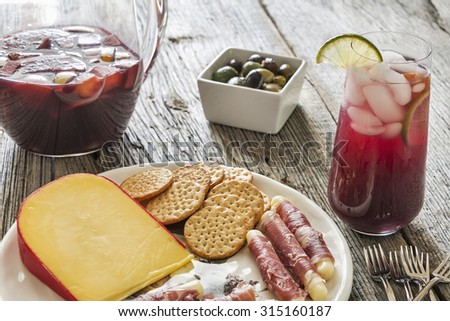 Selective focus was used on this glass of refreshing red sangria made with a variety of healthy fresh fruit.  It is served with appetizers on a rustic weathered wood background. - stock photo