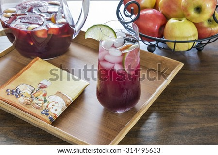 Selective focus was used on this glass of refreshing red sangria.  Traditionally made with red wine and brandy it is filled with fresh fruit like peaches, lemons, limes, oranges, berries and apples. - stock photo