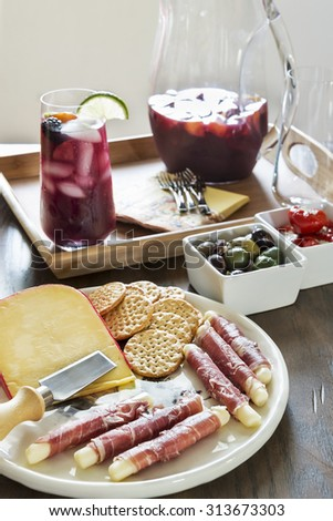 Selective focus was used on this tall glass of refreshing fruit filled red sangria and accompanying tray of cheese and crackers and other delicious hors Dâ??oeuvres. - stock photo