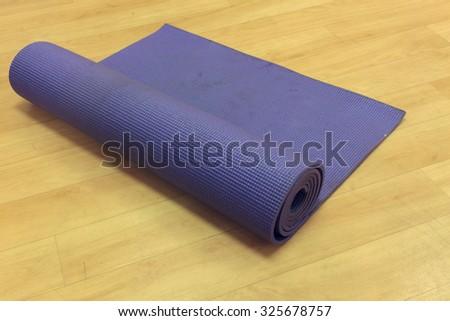 selective focus yoga mat on wood background. - stock photo