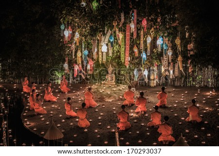 Selective focust at main buddha statue for New year anniversary festival at Chaing mai, Thailand with monk, fire wore and yee peng - stock photo