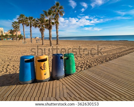 Selective recycling bins on a sunny resort beach - stock photo