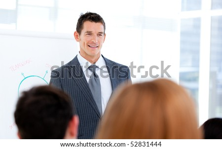 Self-assured businessman doing a presentation to his team - stock photo