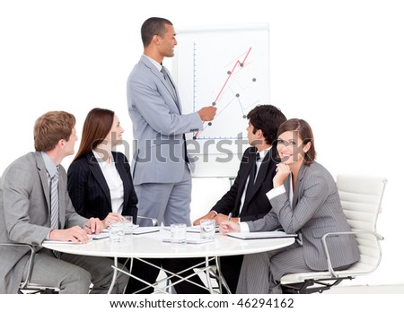 Self-assured businessman reporting sales figures to his team - stock photo