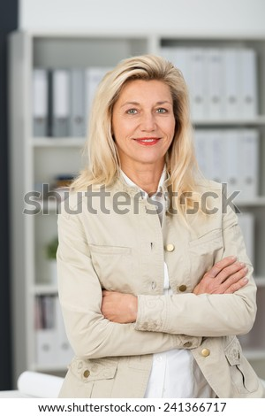 Self-assured friendly attractive middle-aged businesswoman in a stylish jacket standing with folded arms smiling at the camera - stock photo