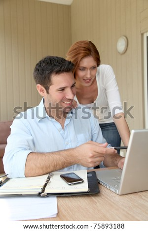 Self-employed man working at home with wife - stock photo