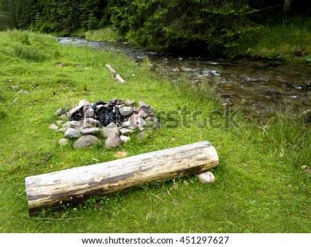 Self-made campfire by the mountain river  - stock photo