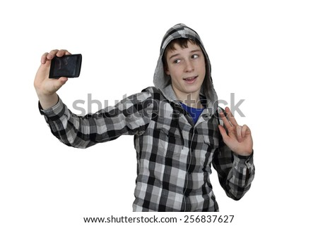 Self photo shot concept - Handsome teenage boy in plaid shirt with hood makes selfie using his cell phone isolated on white background - stock photo