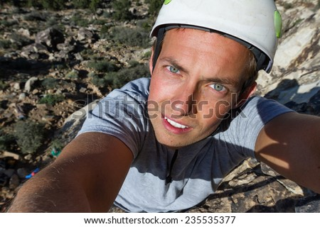 self portrait of a happy young man rock climbing in southern Utah - stock photo