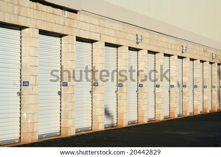 Self storage warehouse metal roll up doors closed in a row. - stock photo