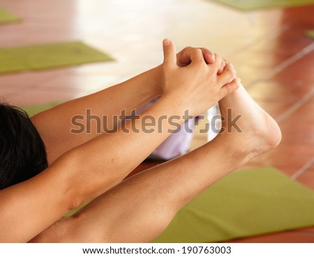 Self yoga stretching legs in bright exercise room - stock photo