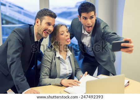 Selfie business team taking pictures in the office. Their tongues - stock photo