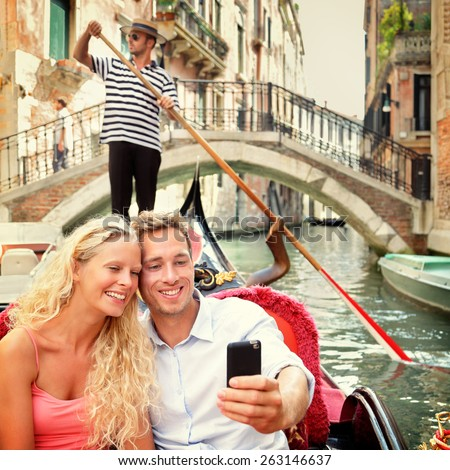 Selfie couple in gondola on Venice travel vacation. Beautiful lovers on a romantic boat ride across the Venetian canals taking self-portrait pictures with smartphone app during their summer holidays. - stock photo