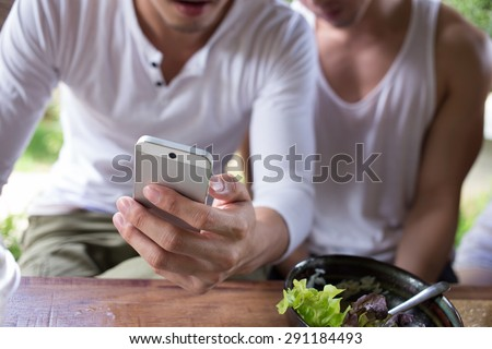 selfie, happy gay couple self portrait with camera on mobile phone, man using app a smartphone playing social network - stock photo