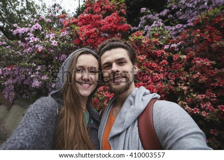 Selfie of a young beautiful couple on the background bright pink and red flowers. Couple smiling. - stock photo