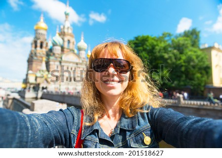 Selfie of a young female tourist on the background of Church of the Savior on Spilled Blood (Cathedral of the Resurrection of Christ) in Saint Petersburg, Russia - stock photo