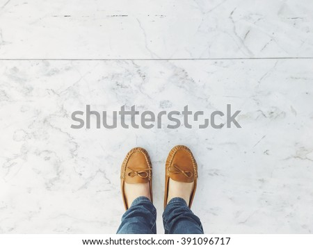 Selfie of feet in leather flat shoes on pavement background, top view - stock photo