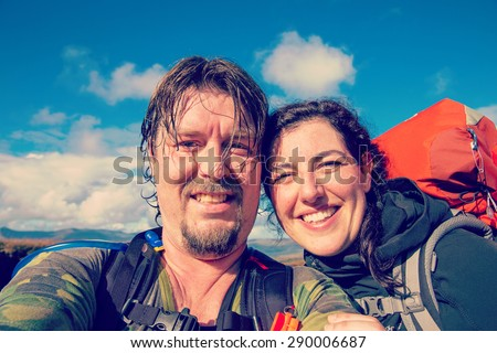 Selfie of hiking couple in the outdoors with filters applied for hipster look - stock photo