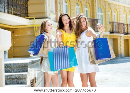 Selfie of three girlfriends near shop. Three attractive young girl holding shopping bags while standing near the store and look at the camera outdoors. Girls laughing and smiling at the camera - stock photo