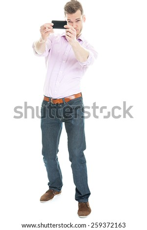Selfie Photo - Full length portrait of a young man taking a selfie with his smart phone, isolated on white background - stock photo