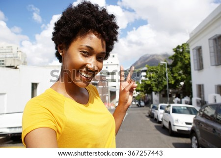 Selfie portrait of smiling young woman standing on the city street gesturing peace sign  - stock photo