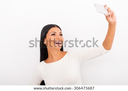 Selfie time! Cheerful young woman making selfie on her smart phone while standing against white background - stock photo