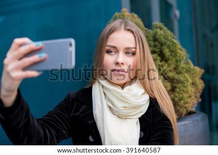 Selfie time. Joyful young women making selfie by her smart phone - stock photo