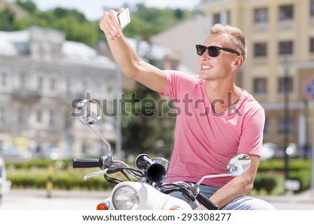 Selfie time. Pleasant young man sitting on scooter and doing selfie. - stock photo