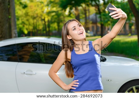 Selfie time. Portrait of attractive young woman standing on background of white car and doing selfie. - stock photo