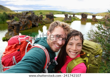 Selfie - travel couple on lake Myvatn Iceland. Friends taking selfies photo having fun traveling together visiting Icelandic tourist destination landmarks. Lake Myvatn lava columns, Iceland. - stock photo