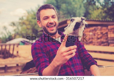 Selfie with llama. Cheerful young man making selfie with llama on his smart phone while standing in the zoo - stock photo