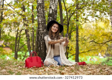Selfie, Young beautiful woman in a hat photographing themselves on a cell phone while sitting in the autumn forest - stock photo