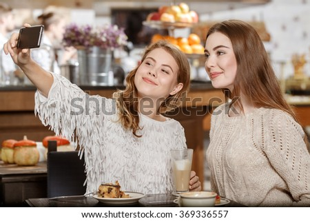 Selfies rule. Shot of two female friends taking selfie together over a cup of coffee smiling cheerfully - stock photo