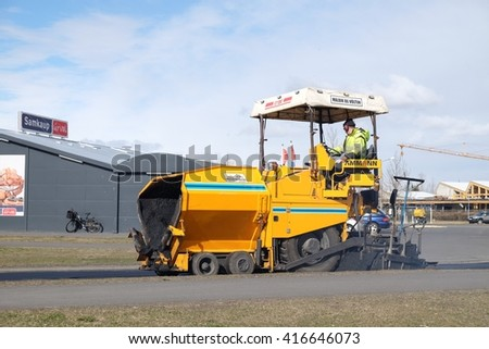 SELFOSS, ICELAND - MAY 4 :Workers operating asphalt paver machine and heavy machinery during repairs road under the program repairs highway road on May 4, 2016 in Selfoss, Iceland. - stock photo