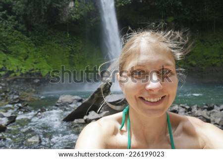 Selfy of a young woman in front of a waterfall - Catarata Rio Fortuna, La Fortuna, Alajuela province, Costa Rica - stock photo
