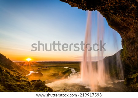 Seljalandsfoss, sunset behind the fall, sunburst and beautiful clear sky. Iceland - stock photo