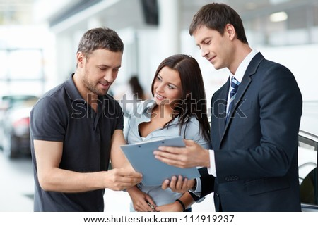 Seller and a couple in the showroom - stock photo