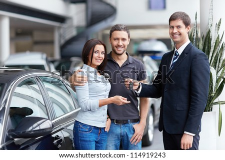 Seller and a couple of with the keys to car - stock photo