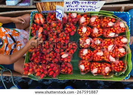 Seller of strawberries and Cherry tomatoes on a boat in a floating market in Bangkok, Thailand - stock photo