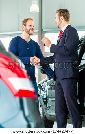 Seller or car salesman and customer in auto dealership, they shaking hands, hands over the car keys and seal the purchase of the auto or new car - stock photo