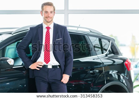 Seller or car salesman in car dealership presenting his new and used cars in the showroom - stock photo
