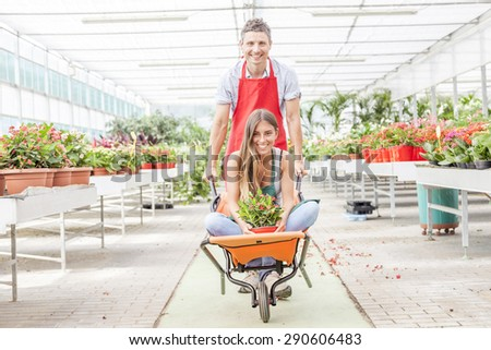 sellers couple have fun pushing the wheelbarrow in a greenhouse - stock photo