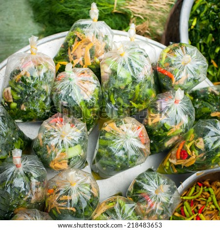 Selling traditional food at asian marketplace. Packed portions of vegetable and meat soup and spicy broth - stock photo